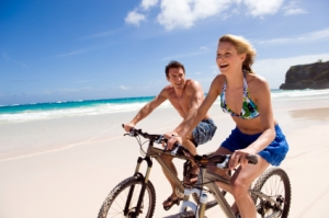 Young couple cycling on a beach